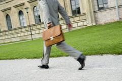 businessman walking with briefcase, low section, (blurred motion) - stock photo