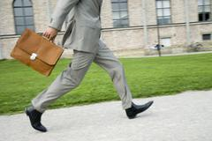Stock Photo of businessman walking with briefcase, low section, (blurred motion)