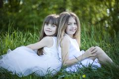 Germany, Bavaria, Two girls (8-9) sitting in meadow, side view, portrait - stock photo