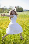 Stock Photo of Germany, Bavaria, Girl (8-9) jumping in meadow, portrait