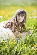 Germany, Bavaria, Girl (8-9) sitting in meadow, portrait - stock photo