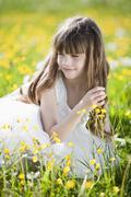 Germany, Bavaria, Girl (8-9) sitting in meadow, portrait Stock Photos