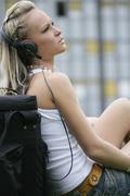 Stock Photo of Germany, Bavaria, Young woman sitting and listening music
