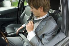 Businessman sitting in car, using seat belt Stock Photos