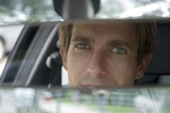 businessman looking into rear view mirror, close-up - stock photo