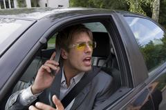 businessman using mobile phone in car, shouting, close-up - stock photo