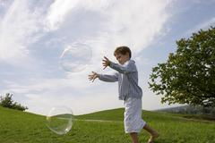 Boy playing with soap bubble Stock Photos