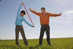 young couple exercising with resistance band - stock photo