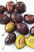 Entire and sliced plums, elevated view Stock Photos