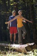 Stock Photo of couple balancing on tree trunk