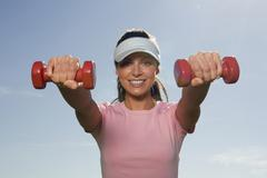 young woman exercising with dumbbells, smiling, close-up - stock photo