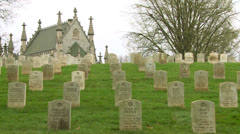 A 19th century cemetery is framed by a church on a hill. Stock Footage