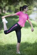 Stock Photo of Germany, Bavaria, Woman stretching on meadow