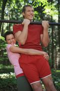 Stock Photo of young couple exercising on horizontal bar, smiling