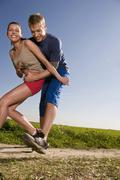 Young couple jogging, man catching woman Stock Photos