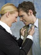 Businesswoman grabbing man by tie, shouting, side view, close-up Stock Photos
