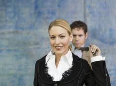Stock Photo of businesswoman pulling businessman's tie, smiling