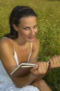 Germany, Bavaria, Woman sitting in a meadow with book - stock photo