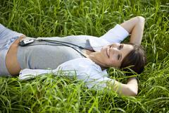 Stock Photo of Germany, Bavaria, Young woman in meadow using mp3 player, smiling, portrait