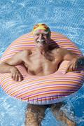 Austria, Senior man with floating tire in swimming pool, smiling, portrait - stock photo