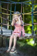 Germany, Bavaria, Girl (4-5) on playground sitting on suspension bridge, Stock Photos