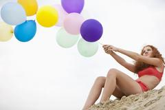 Germany, Bavaria, Young woman on sand dune holding bunch of balloons Stock Photos