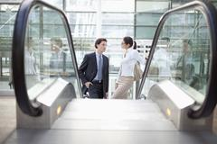 Germany, Bavaria, Munich, Airport, Businesspeople standing on escalator - stock photo