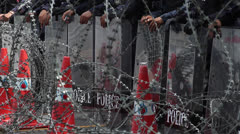 RIOT POLICE SECURITY BARRIER RAZOR WIRE DANGER Stock Footage
