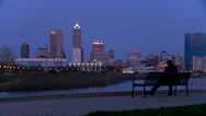 Stock Video Footage of A man sits on a park bench overlooking the city of Indianapolis at dusk.