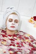 Woman taking a blossom bath, portrait Stock Photos