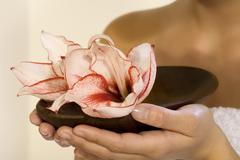 Woman holding a bowl with orchid blossoms - stock photo
