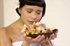 Young woman holding bowl with orchid blossoms, portrait - stock photo
