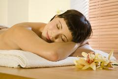 Young woman lying in spa, eyes closed Stock Photos