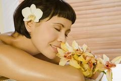 Young woman holding bowl of flowers, eyes closed - stock photo