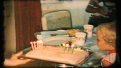 Twins take turns blowing out birthday cake candles, 94 vintage film home movie Stock Footage