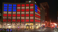 Stock Video Footage of An office building is lit up at night with the American flag.