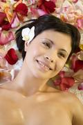 Young woman lying down with rose petals - stock photo
