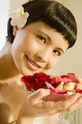 Young woman holding bowl of rose petals, smiling - stock photo