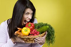 Dark-haired woman holding basket with vegetables, fooling about - stock photo