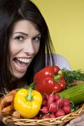 Dark-haired woman with vegetables, fooling about, portrait - stock photo