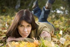 Brunette woman relaxing on autumn foliage, portrait Stock Photos