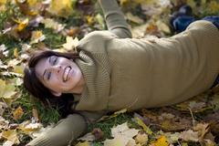 Brunette woman relaxing on autumn foliage, portrait Stock Photos