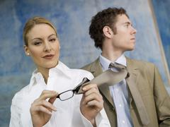 Business woman cleaning spectacles with man´s tie Stock Photos