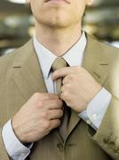 Stock Photo of young businessman adjusting tie, mid section, close-up