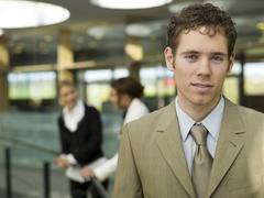 Young businessman, portrait, women in background Stock Photos