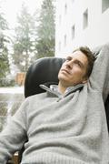 man sitting in armchair looking upwards - stock photo