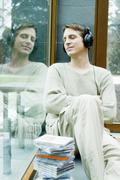 Young man with headphones relaxing on window sill Stock Photos
