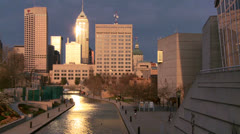 Wide shot of Indianapolis Indiana river walk at dusk with sun glinting off Stock Footage
