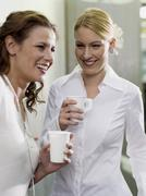 Two women holding paper cups Stock Photos