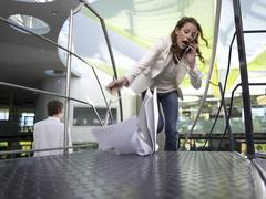 Stock Photo of young businesswoman using mobile phone, papers falling on floor